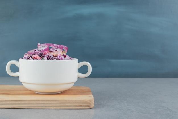 Нарезанный фиолетовый лук и салат из капусты в керамических чашках.