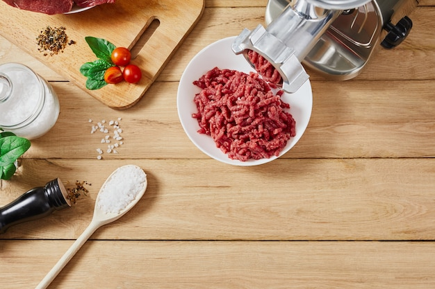 Chopped raw meat and ground beef . the process of preparing forcemeat by meat grinder. top view.