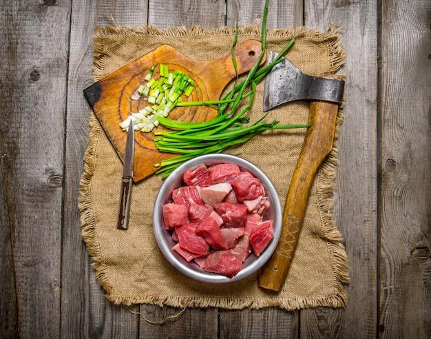 신선한 양파와 다진 생고기와 나무 테이블에 오래된 직물에 도끼