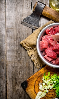 Chopped raw meat with fresh onions and an axe on an old fabric on a wooden table