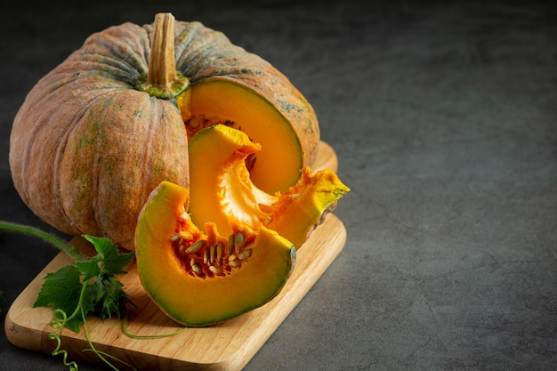 Chopped raw pumpkin put on wooden cutting board Free Photo