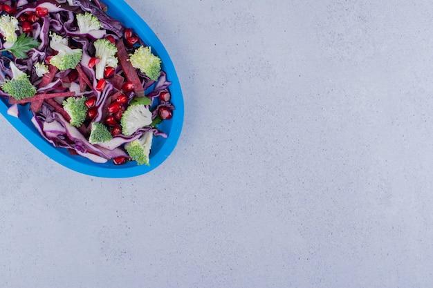다진 붉은 양배추와 브로콜리 샐러드가 대리석 배경에 석류 가오리와 섞였습니다. 고품질 사진