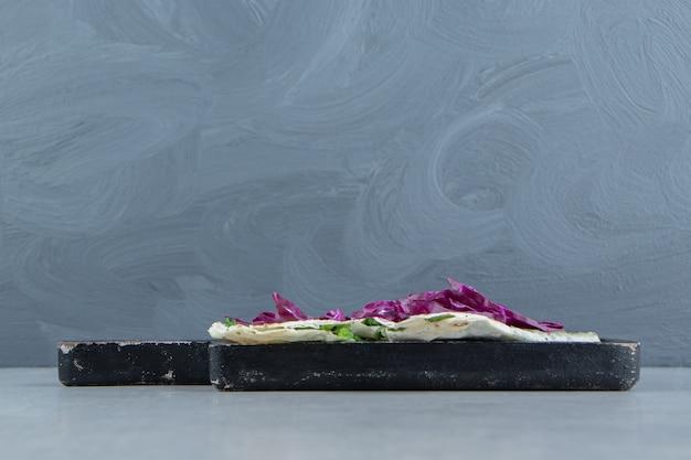 Cavolo rosso tritato e gutabs sul vassoio, sullo sfondo di marmo.