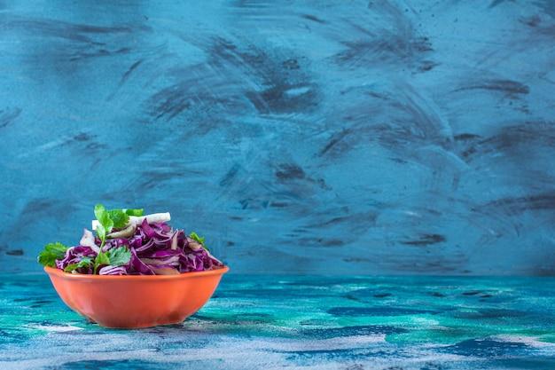 Нарезанная краснокочанная капуста, петрушка и редис в миске