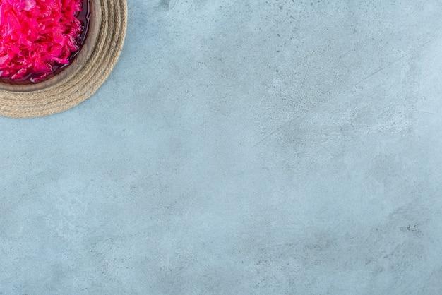 Crauti fermentati rossi tritati in una ciotola su un sottopentola, sul tavolo blu.