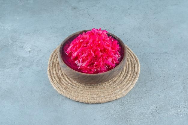 Нарезанная красная квашеная капуста в миске на подставке, на синем столе.