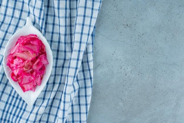 파란색 테이블에 있는 삼발이 위에 있는 그릇에 다진 붉은 발효 소금에 절인 양배추.