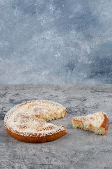잘게 잘린 둥근 맛있는 케이크가 대리석 테이블에 놓여 있습니다.