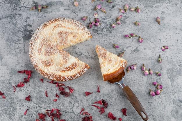 大理石のテーブルの上に置かれたみじん切りの丸いおいしいケーキ。