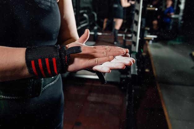 강도 훈련 전에 분필 가루로 손을 박수 젊은 여성 운동 선수의 다진 샷