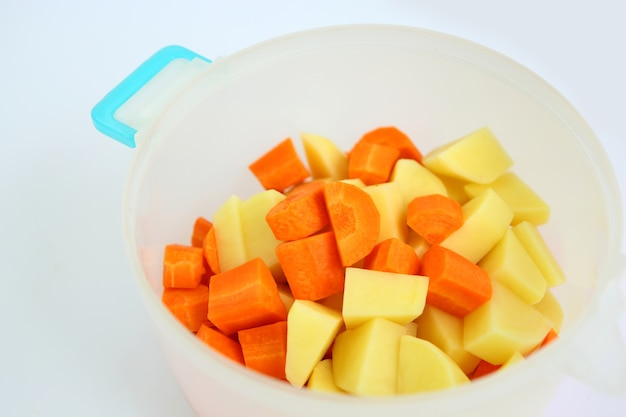 Chopped and sliced carrot and potatoes in plastic pot
