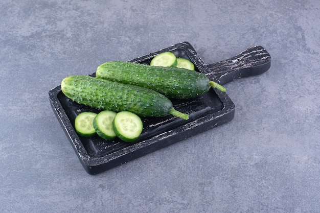 Chopped and sliced green cucumbers on a wooden board