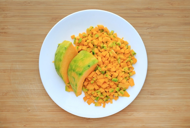 Chopped and sliced japanese pumpkin on white plate against wood board background.