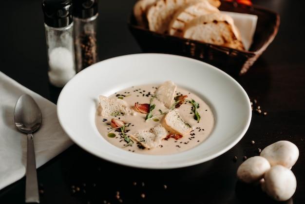 白い皿にきのことパン粉を入れたみじん切りスープ