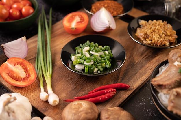 Cipollotto tritato su un piatto nero con peperoncino, pomodori e aglio