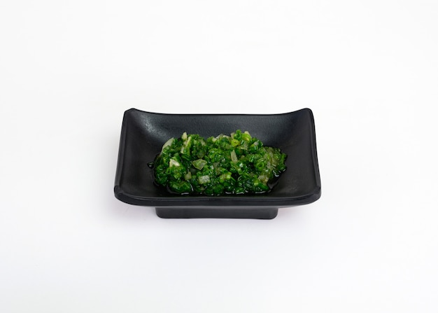 Chopped spring onion or chives pickled sauce in black cup Premium Photo