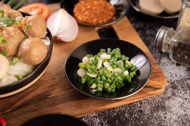 Нарезанный зеленый лук на черной тарелке с чили, помидорами и чесноком