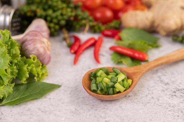 Нарезанный зеленый лук на деревянной ложкой с перцем и помидорами на белом цементном полу.