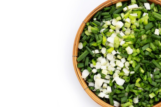 Chopped spring onions in bamboo basket on white background.