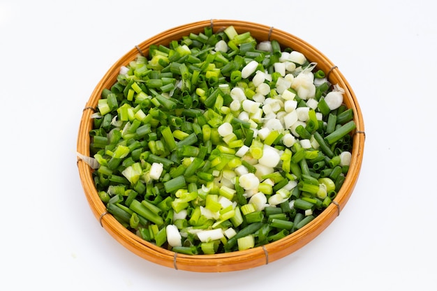 Chopped spring onions in bamboo basket on white background