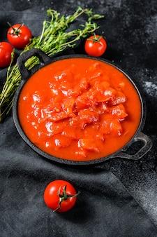 鍋に刻んだ缶詰の赤いトマト。黒の背景。上面図。