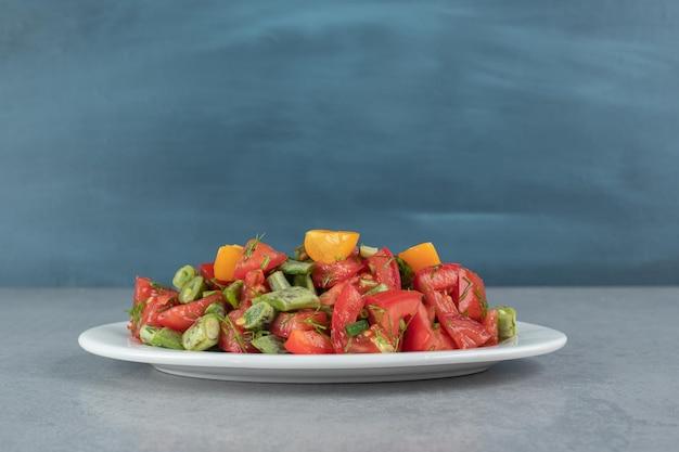 Insalata di pomodori tritati con fagioli ed erbe aromatiche.