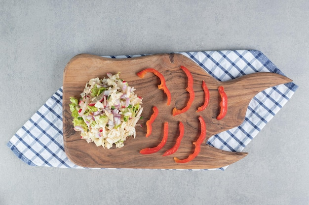 Chopped vegetable and fruit salad on a wooden board.