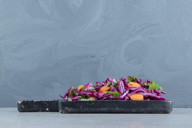 大理石の上に、木の板に刻んだ野菜サラダ。