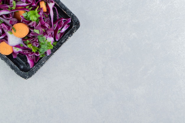 Chopped vegetable salad in the wooden board , on the marble background.
