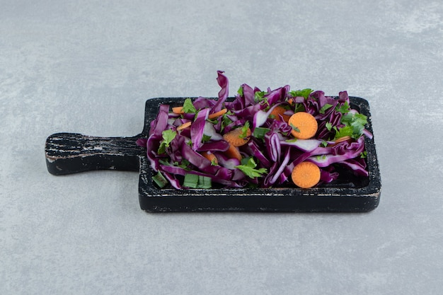 Chopped vegetable salad in the wooden board , on the marble.