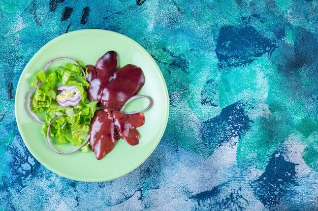 Нарезанные овощи и субпродукты на тарелке