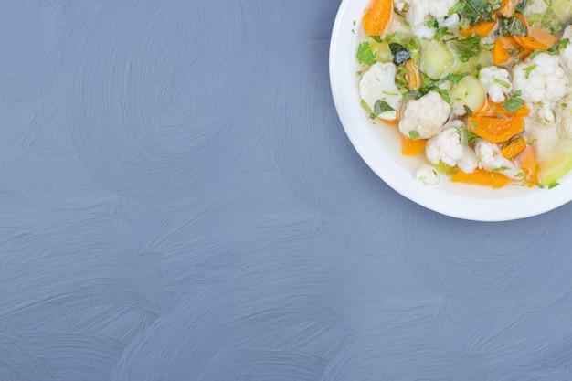 흰 접시에 국물 수프에 다진 야채