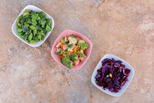 Нарезанные овощи смешать и сложить в миски на полотенце на мраморной поверхности.