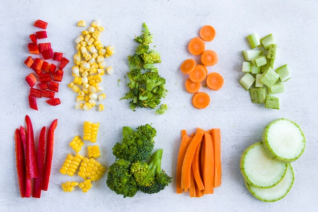 Chopped vegetables on the white table, carrot, broccoli, corn and bell pepper