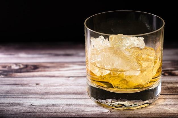 소박한 나무 테이블에 위스키 또는 스카치와 큰 얼음 덩어리가 든 유리의 잘게 잘린 보기