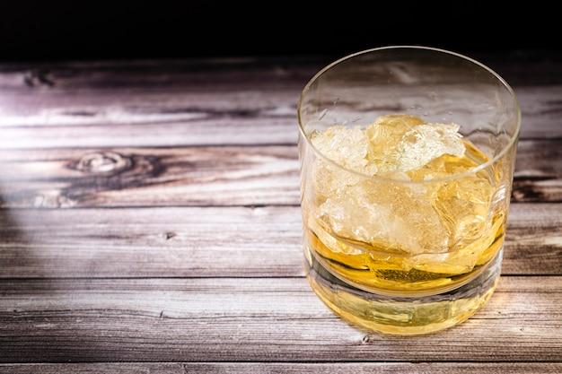 素朴な木製のテーブルの上にウイスキーまたはスコッチと氷の大きな塊とガラスの切り刻まれたビュー