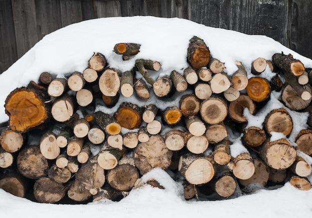 みじん切りの木。雪の中で屋外の木の丸太の山