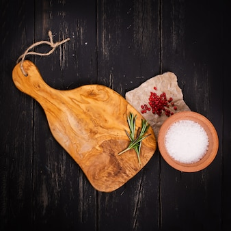 Chopping board, seasonings and rosemary on dark wooden background. square image