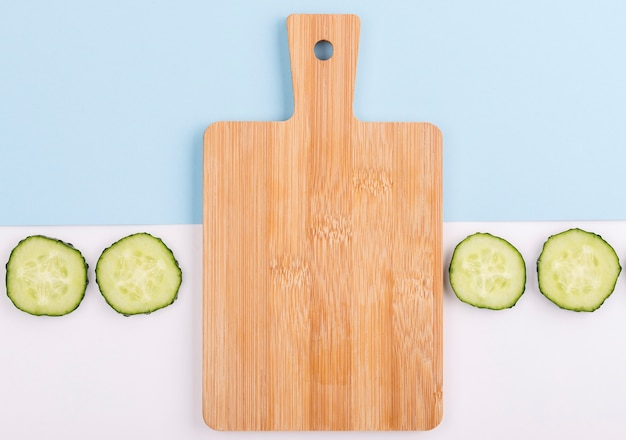 Chopping board surrounded by cucumber slices