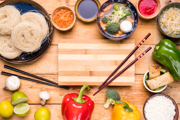 Chopping board with chopsticks spread with traditional thai food