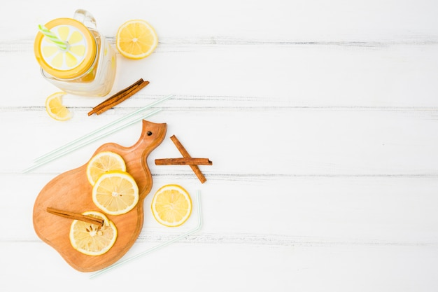Chopping board with lemons near cinnamon and straws with glass