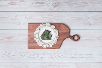 Chopping board with ornament plate and green leaves