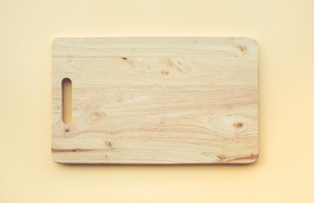 パステルカラーの背景に木製まな板