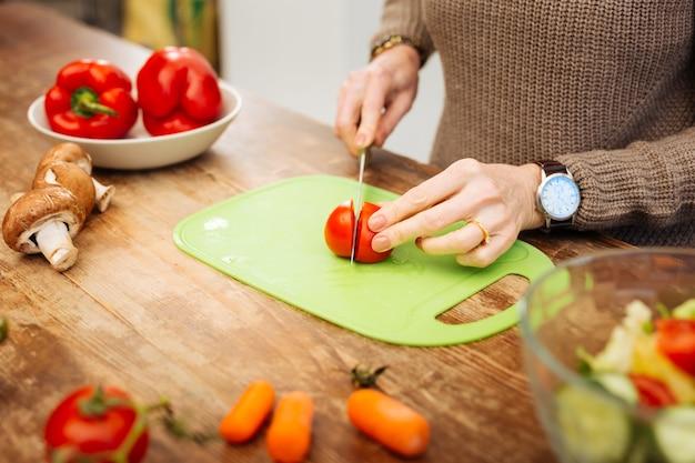Нарезать помидор. внимательная зрелая женщина с часами на запястье режет овощи для простого салата