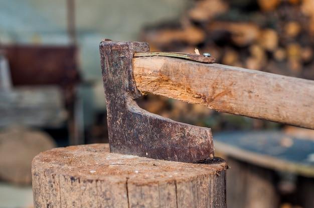 木を斧で刻む。斧は木の柱の中に詰まっていた。古い、摩耗した、傷ついた、鋭い斧の木の上に立って、切れた木の背景に木の切れ端。