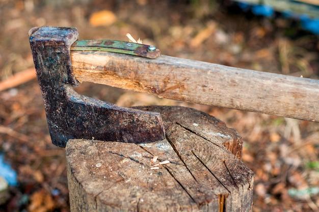 Измельчая древесину топором. топор застрял в деревянном бревне. старый, изношенный, поцарапанный, острый топор, стоящий на деревянном, потрескавшемся пеньке на фоне измельченной древесины. Бесплатные Фотографии