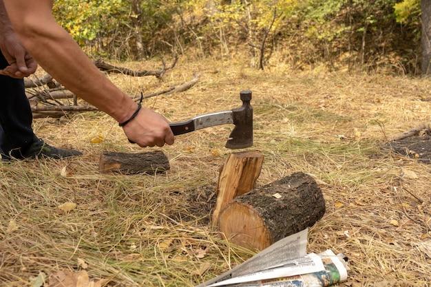 Рубить дрова топором, чтобы развести костер в лесу. у костра на природе