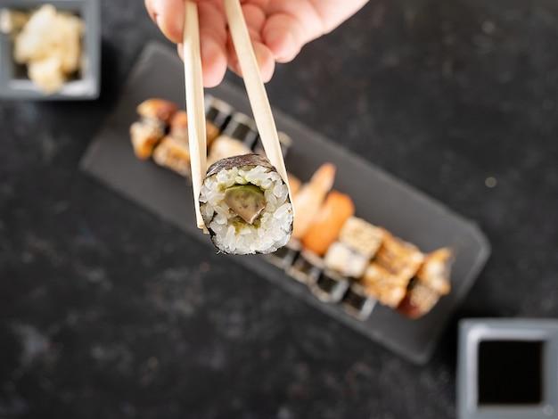 Палочка для еды с суши в фокусе и смесь суши на темном каменном фоне на столе не в фокусе. здоровая кухня
