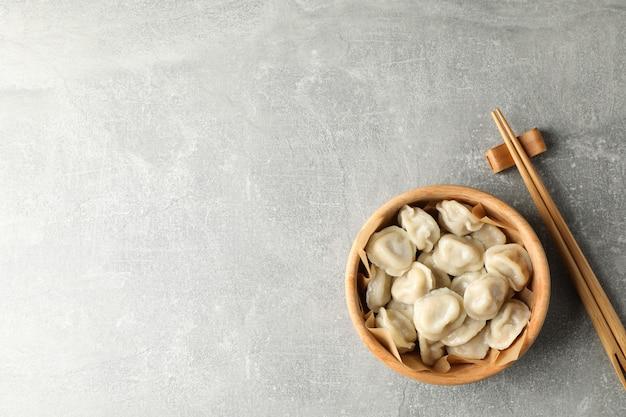 箸と灰色の背景、テキスト用のスペースに餃子とボウル