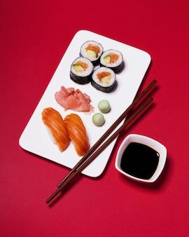 Палочки для еды и приправы возле суши на красном